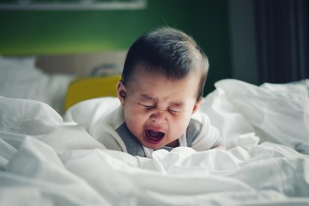 疝痛気分のために泣いている少年。