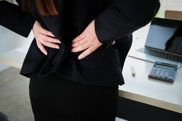 Работницы показывают боль в пояснице от работы.