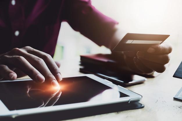 オンライン決済、男はデジタルタブレットを使用して、オンラインショッピングのためのクレジットカードを持っている手。ブラックフライデーまたはサイバー月曜日の概念。