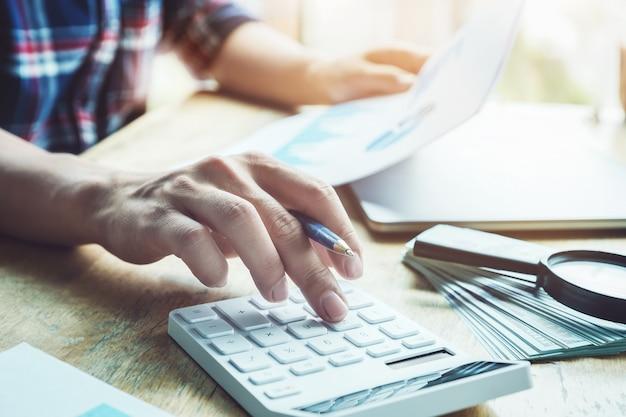 会計士は計算するために計算機を押して投資予算の正確さをチェックしています