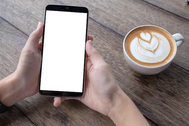 カフェでスマートフォンを使ってビジネス女性。スマートフォンまたは携帯