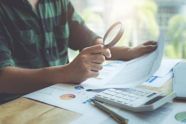 拡大鏡を使用してバランスシートを確認するビジネスマン