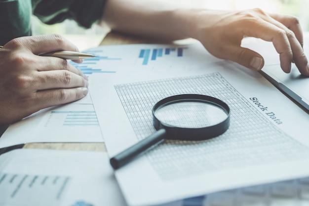 拡大鏡を使用して貸借対照表を確認するビジネス男