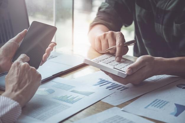 Бизнес и партнерство обсуждают с помощью калькулятора для обзора годового баланса с ручкой удерживания и использования портативного компьютера для расчета бюджета. проверка целостности перед инвестиционной концепцией.