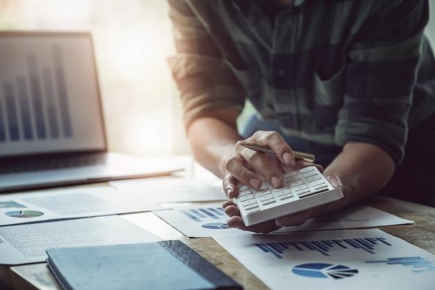 ビジネスマンのバランスを計算するためにラップトップコンピューターを使用して年次貸借対照表を確認するために計算機を使用してペンを保持しています。投資の概念の前に監査とチェックの整合性。
