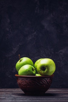 粘土ボウルのテーブルの上のコピースペースとリンゴ