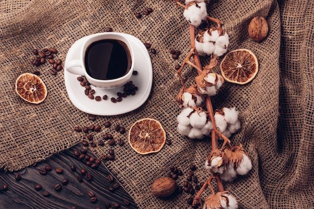 ボウルにコーヒーと綿のテーブルの上のコーヒー豆のある静物