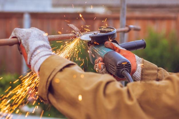 Рабочий режет металлический шлифовальный станок. красивые искры летят из-под режущего диска