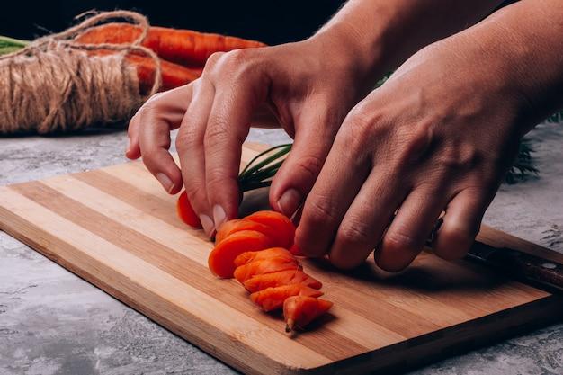 女性の手は新鮮なニンジンのスライスを希釈します