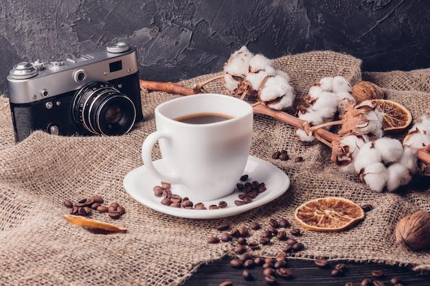 白いコーヒーカップとレトロなカメラの横にある綿