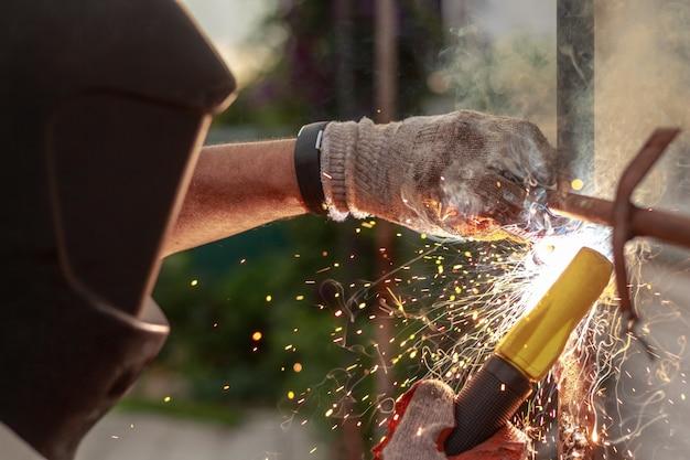 労働者は金属要素の溶接に従事しています