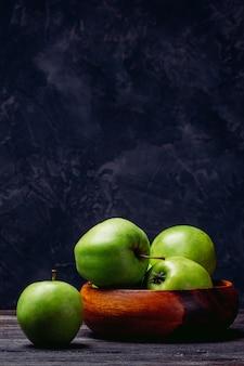 りんごはテーブルの上のボウルで緑色です