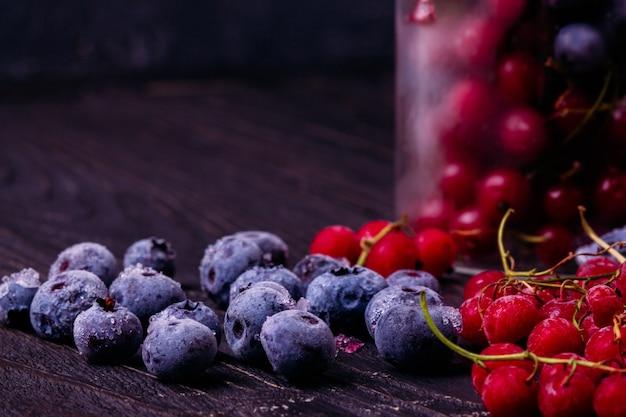 赤スグリとテーブルの上の霜のブルーベリー
