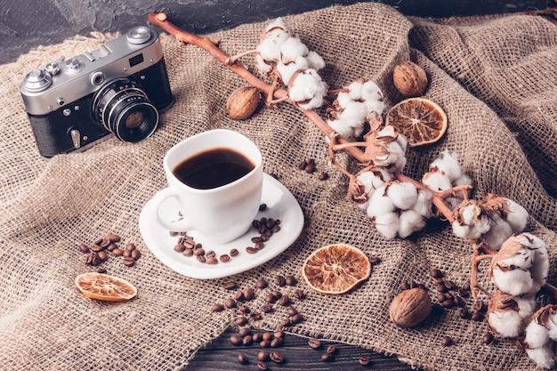一杯のコーヒーのレトロなカメラと綿
