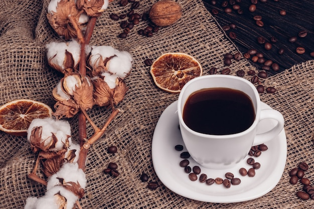 解任に綿入りのコーヒーカップの横にあるコーヒーの穀物