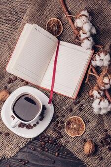 メモ帳とフラットスタイルのコットントップビューでカップのコーヒー