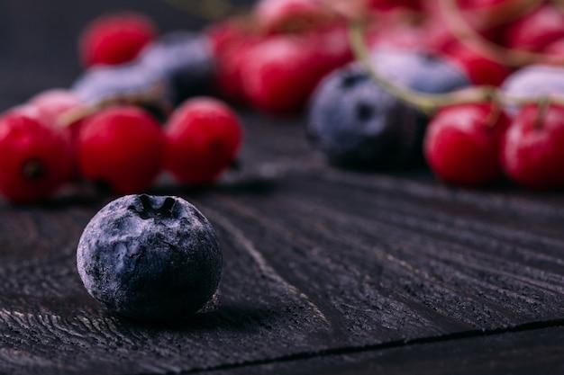 木製のテーブルのクローズアップの背景に霜で冷凍ベリーブルーベリーブルーベリー