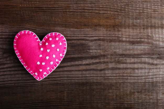 Розовое сердце из фетра на деревянном столе