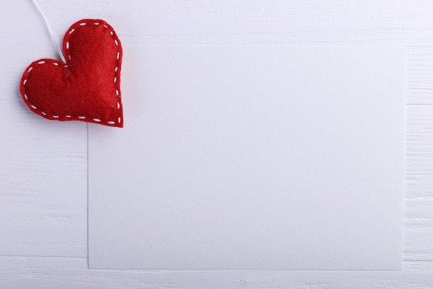 木製テーブルの上の白い紙の横にある手作りの赤いフェルトハート