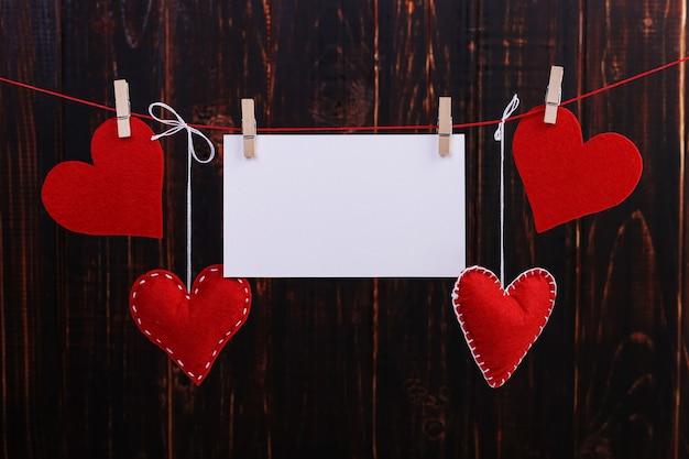 Красные фетровые сердечки ручной работы и белая бумага висят на веревке с прищепками