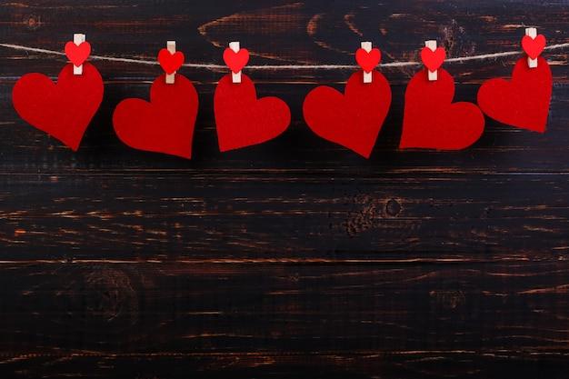 黒い木製の背景に洗濯はさみでロープに赤いハート。テキストのための場所、スペースをコピーします。