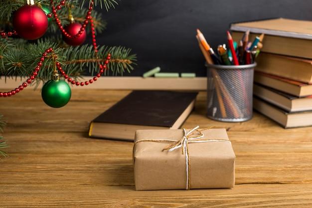 書籍、オーガナイザー、黒板を備えたギフト教師用テーブル。クリスマスと新年の概念。