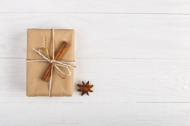 Подарок крафт-бумаги с корицей и звездчатого аниса на белом столе.