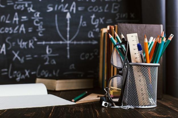Парта в классе, с книгами на фоне классной доски с письменными формулами
