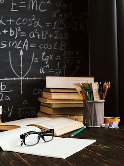 書かれた式とチョークボードの背景に関する書籍の教室でのスクールデスク