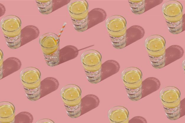 氷とレモンの冷たい水のグラス。ピンクの背景に繰り返しパターン。