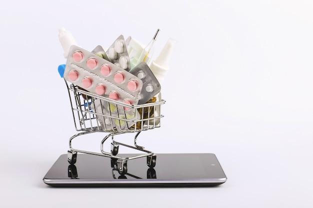薬や薬と一緒に買い物カゴがスマートフォンにあります。オンライン販売の概念