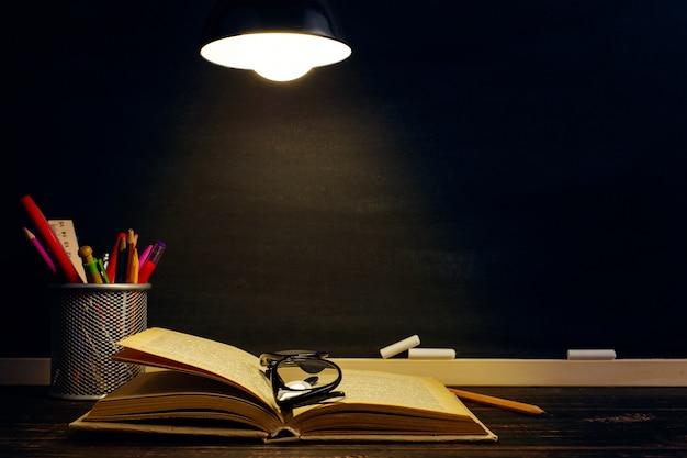 Стол учителя, на котором лежат письменные принадлежности, вечером под лампой.