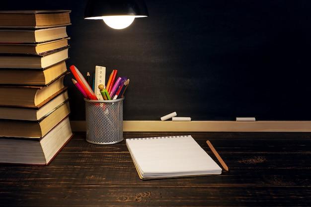 夕方、ランプの下で、筆記用具が置かれている先生の机。
