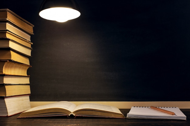 Письменный стол на фоне меловой доски, книги, тетради и ручки, в темноте при свете лампы.