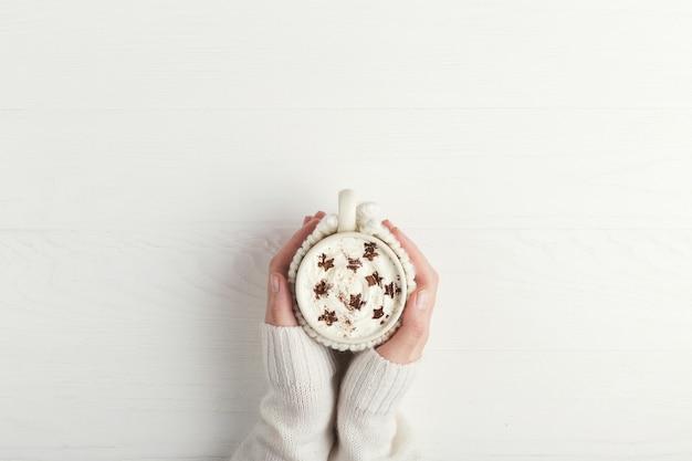 女の子は星の形のホイップクリームとパウダーで、熱い冬の飲み物のカップを保持しています。