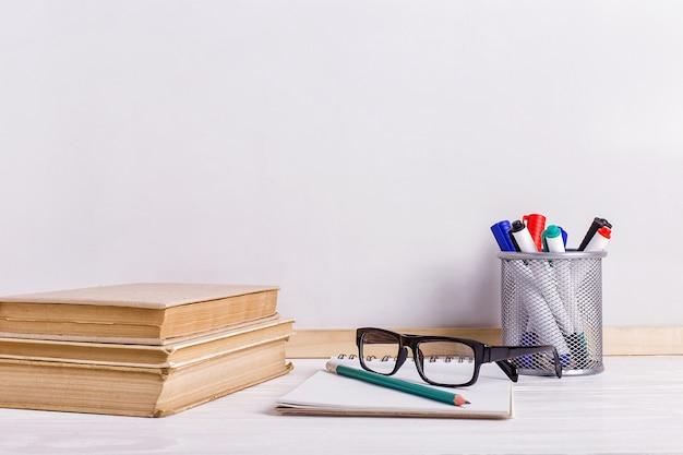 テーブルの上の本、マーカー、ノート、鉛筆、眼鏡