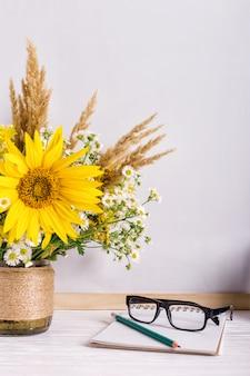空のテーブルに木製チョークボードフレームと花瓶の花束