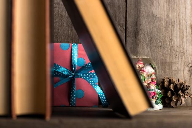 Подарок спрятан на деревянной полке за книгами.