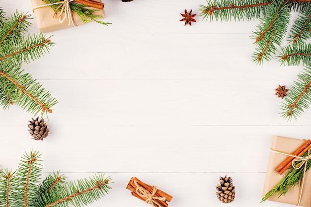 Подарки и еловые ветки образуют рамку-заготовку для рождественской открытки. , вид сверху.