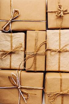 Подарки из крафт-бумаги плотно прилегают друг к другу на белом столе на рождественском фоне.