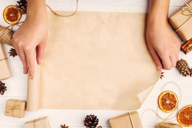 女性の手は、白いテーブルの上の乾燥オレンジ、シナモン、松ぼっくり、アニスの背景にクラフトペーパーロールを回しています。 、上面図、テキストのための場所。