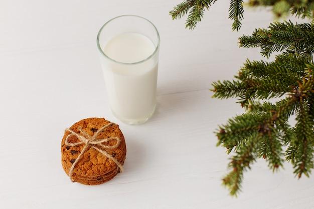 クリスマスツリーの下のサンタクロースのミルクとクッキー