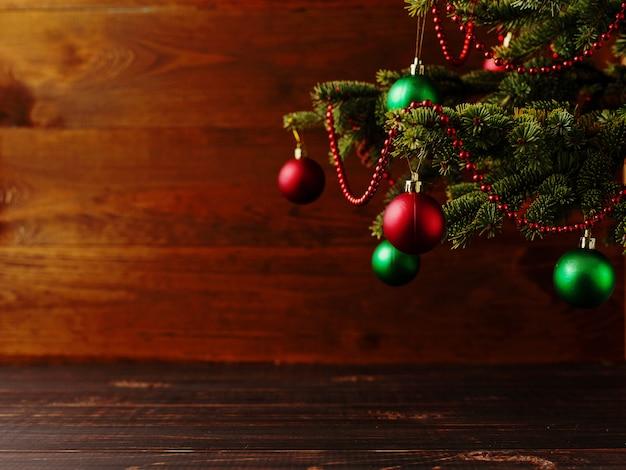 Рождественская елка, наряженные шарики, стоит на деревянном столе.