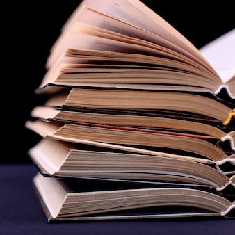Открытые книги сложены на столе на черном, изолировать. сложная домашняя работа в школе, гора знаний.