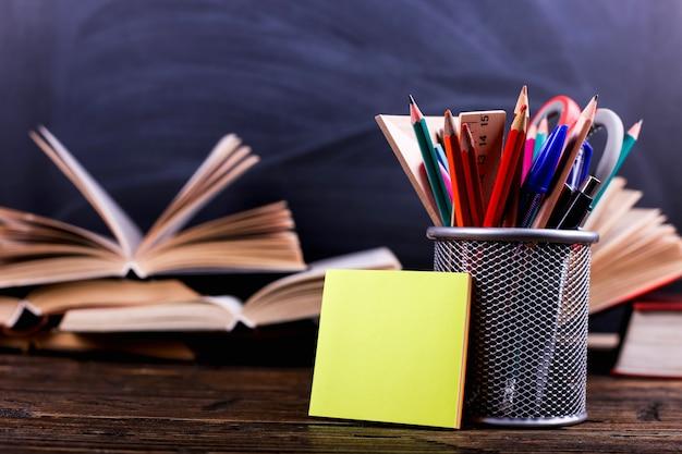ノートブック、開いた本、チョークボードの上の暗い木製のテーブルの上にペンのスタンド。学校での知識の学習、ステッカーコピースペース。