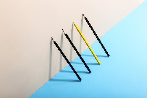 鉛筆が壁に立ち、影を落とし、幾何学的な形を描きます。