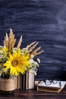 書籍、メガネ、マーカー、白い花瓶の花の花束