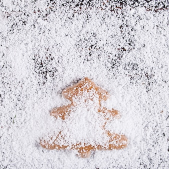 クリスマスコンセプトの背景、白い雪に不満の木製テーブルの上のクリスマスツリーの形をした手作りのジンジャーブレッド