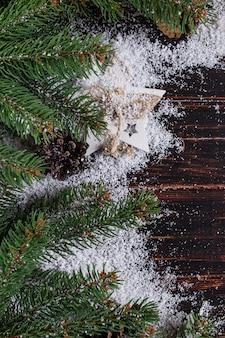 クリスマスの背景、モミの木、木製テーブルの上の円錐形、白い雪、コピースペース、トップビューで粉砕。