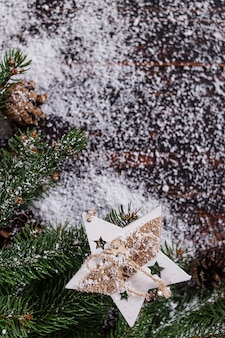 クリスマスコンセプトの背景、手作りの星飾り、木製のテーブルの上の緑のクリスマスツリー、白い雪で破線